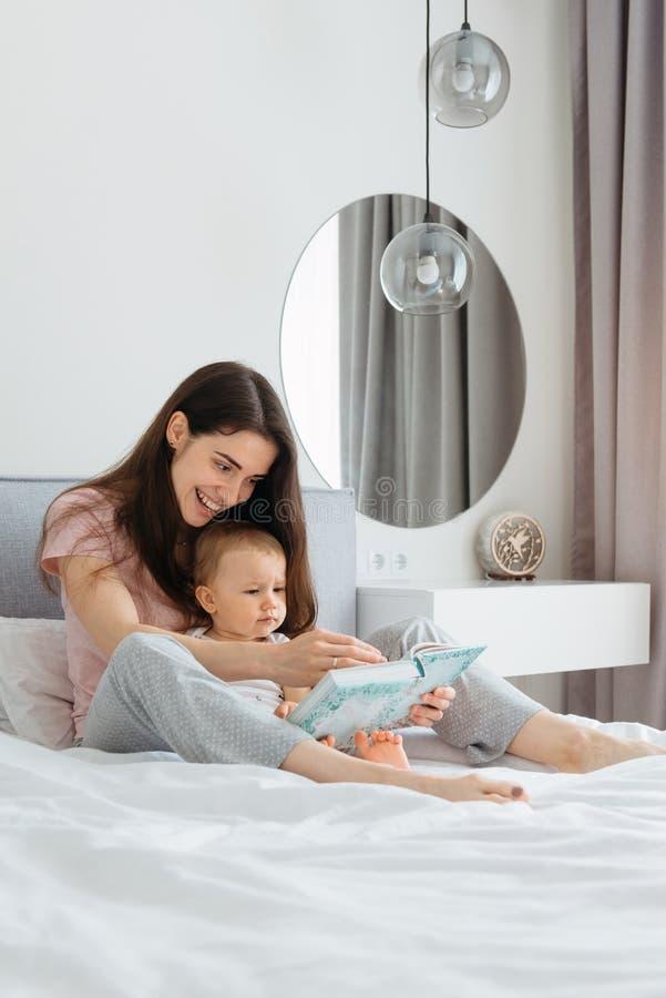 Matki i berbecia c?rki czytelnicza bajka rezerwuje w sypialni obraz stock