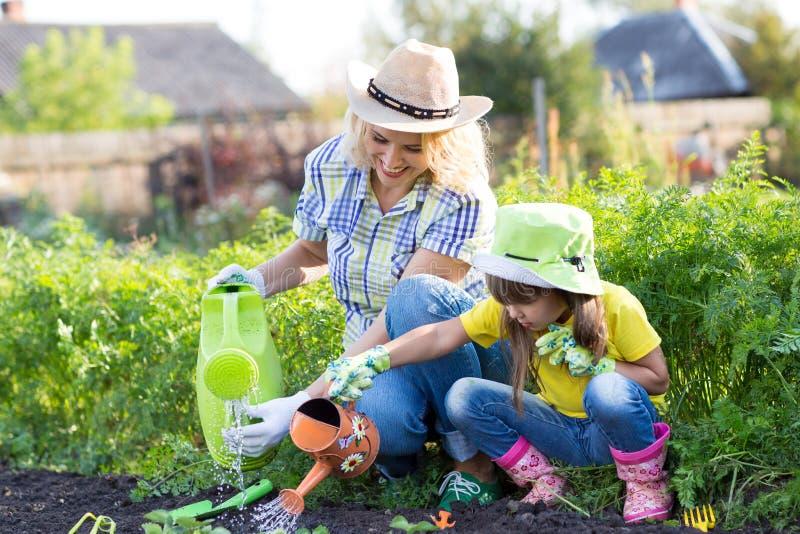 Matki i berbecia córki podlewanie i ogrodnictwo zdjęcia royalty free