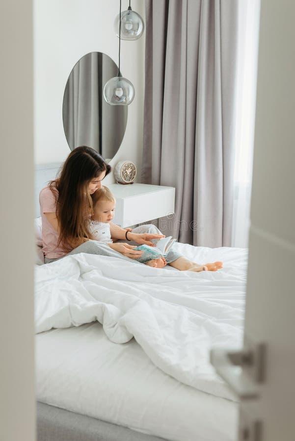 Matki i berbecia c?rki czytelnicza bajka rezerwuje w sypialni obrazy stock