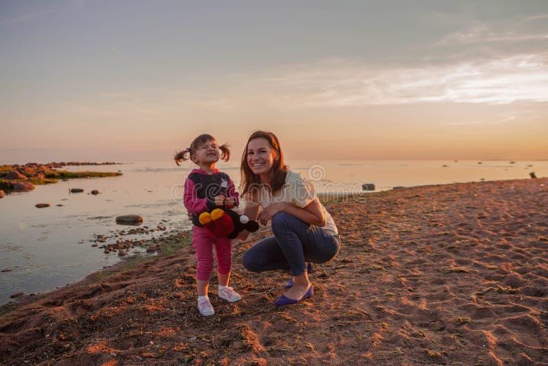 Matki i córki odprowadzenie wzdłuż plaży przy zmierzchem Pojęcie szczęśliwa życzliwa rodzina zdjęcie stock