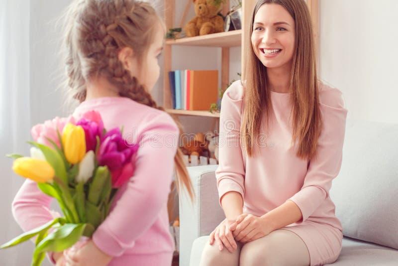 Matki i córki mamy ` s dziewczyny urodzinowy mienie obok wiązki tulipany wpólnie w domu zdjęcia stock