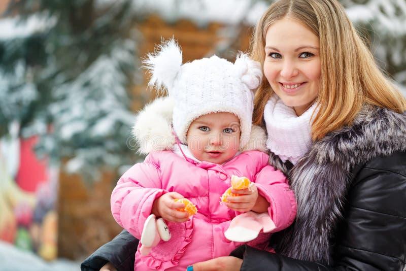 Matki i córki mandarynka zabawnie kierowcy sledge zimy obraz royalty free