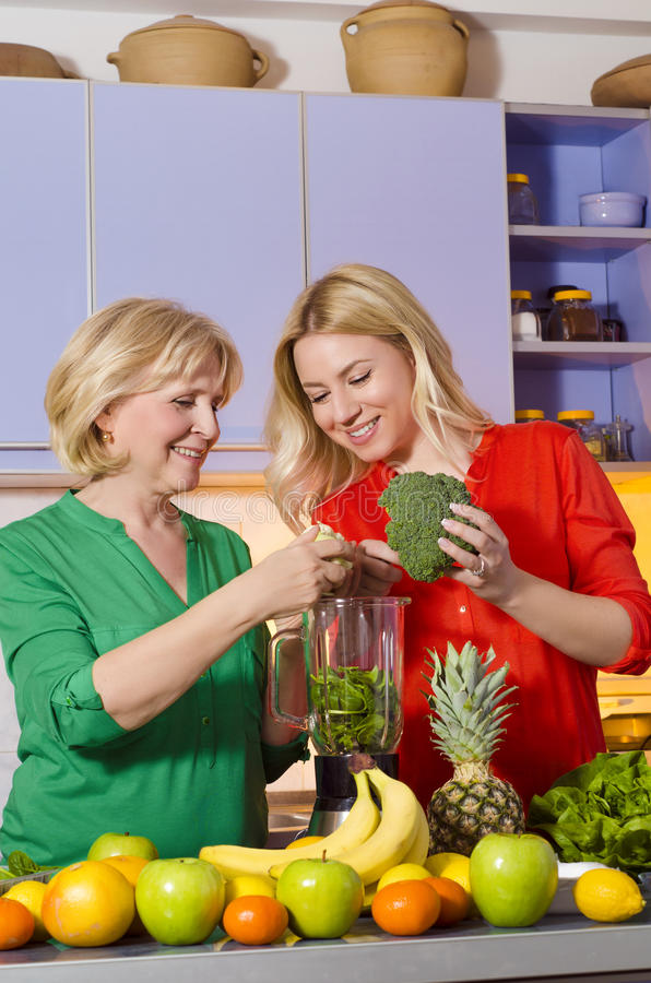 Matki i córki narządzania owoc dla robić świeżemu sokowi fotografia royalty free