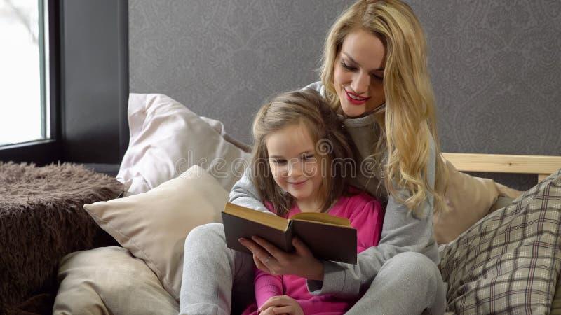 Matki i córki obsiadanie na łóżku w książka fotografia royalty free