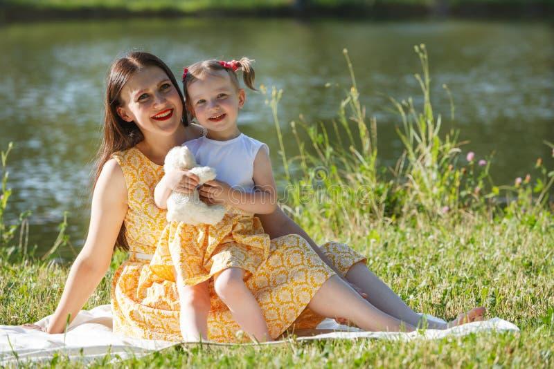 Matki i córki obsiadanie na białej koc Dziewczyna trzyma białego niedźwiedzia Spojrzenie w odległość W tła jeziorze zdjęcia stock