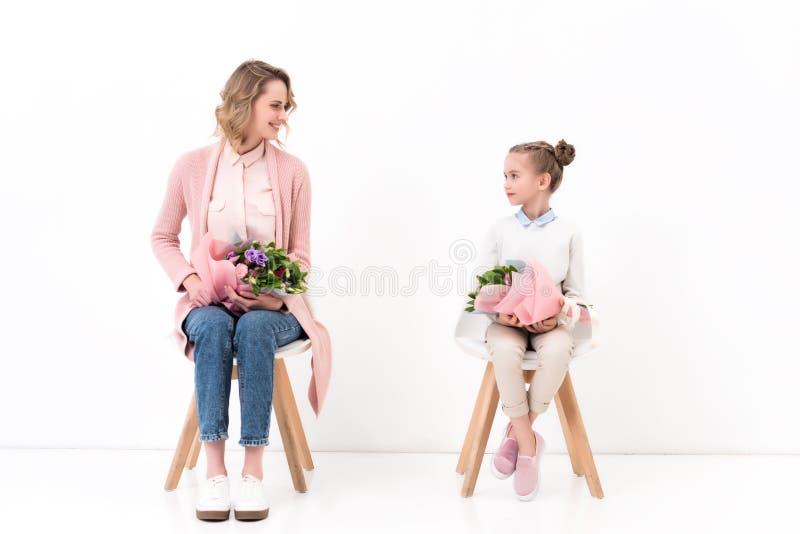 matki i córki obsiadanie na krzesłach z bukietami kwiaty, szczęśliwe matki zdjęcia stock