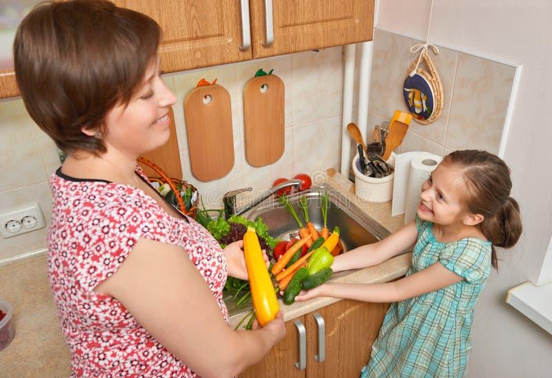 Matki i córki płuczkowi warzywa i świeże owoc w kuchennym wnętrzu, zdrowy karmowy pojęcie obraz stock