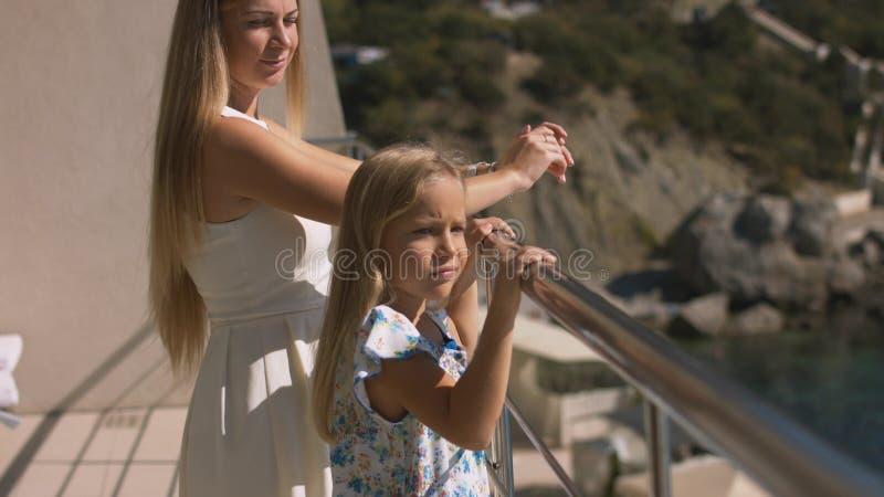 Matki i córki pozycja na otwartym balkonie przegapia morze fotografia stock