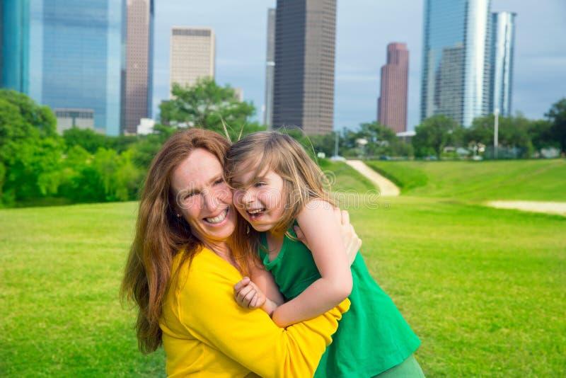 Matki i córki szczęśliwy uściśnięcie śmia się w parku przy miasto linią horyzontu zdjęcie stock