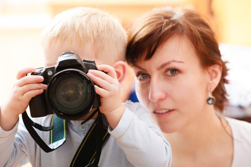 Matki i chłopiec dziecko żartuje syna z kamerą bierze fotografię. W domu. zdjęcie royalty free