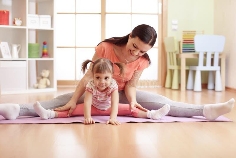Matki i dziecka córka robi sprawności fizycznych ćwiczeniom na macie w domu obraz stock