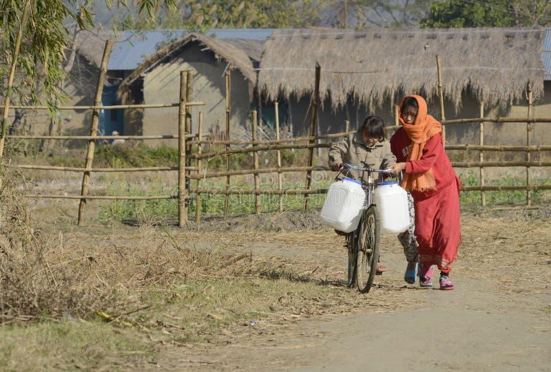 Matki i dziecka działania przewożenia woda w jerry puszce na obrzeże wiosce fotografia royalty free