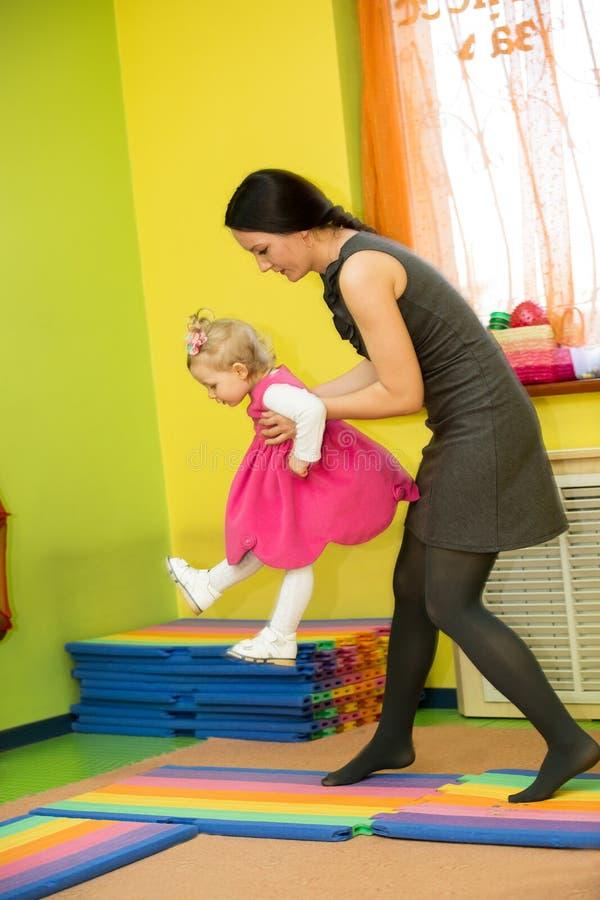 Matki i dziecka dziewczyna bawić się w dziecinu w Montessori preschool obraz stock