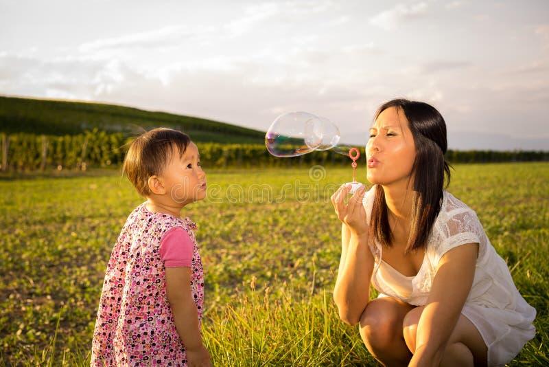 Matki i dziecka plenerowy bawić się z mydlanymi bąblami obrazy royalty free