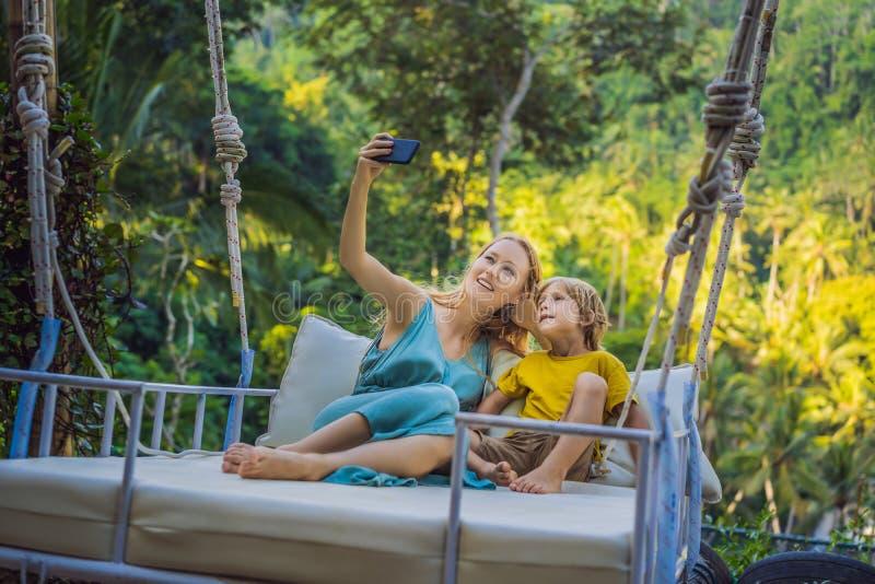 Matki i syna chlanie w dżungla tropikalnym lesie deszczowym Bali wyspa, Indonezja Hu?tawka w zwrotnikach Huśtawki - trend Bali obraz stock