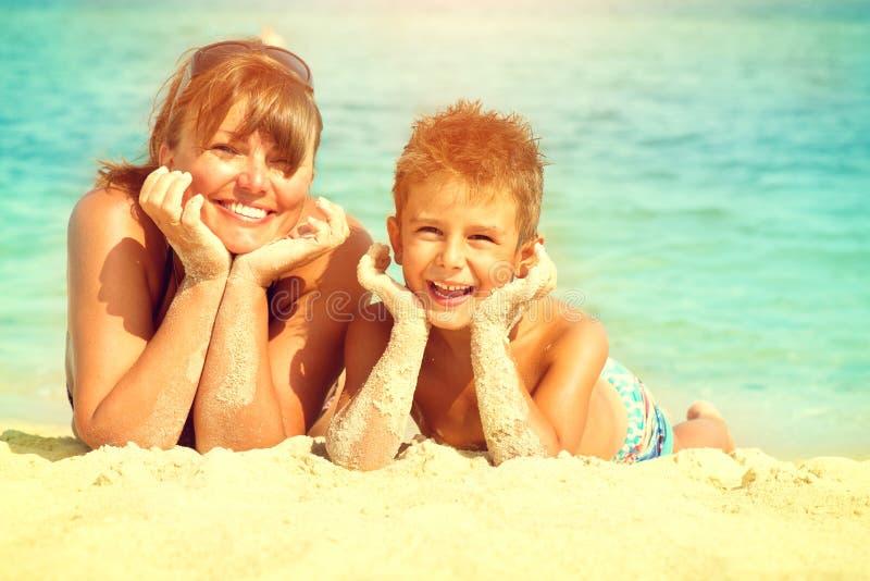 Matki i syna lying on the beach przy plażą zdjęcia stock