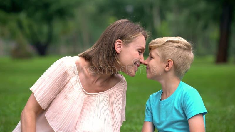 Matki i syna nuzzling, wydaje czas wpólnie outdoors, jedność kochająca rodzina zdjęcie royalty free