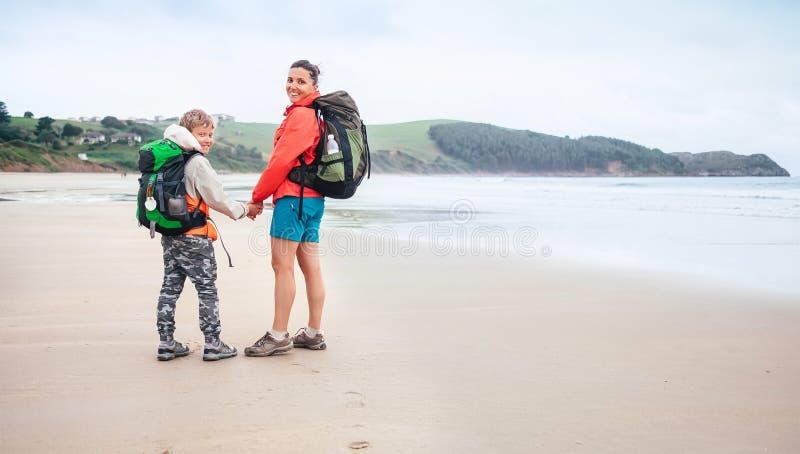 Matki i syna podróżnicy chodzą na osamotnionej ocean plaży przy dżdżystą sumą obraz stock