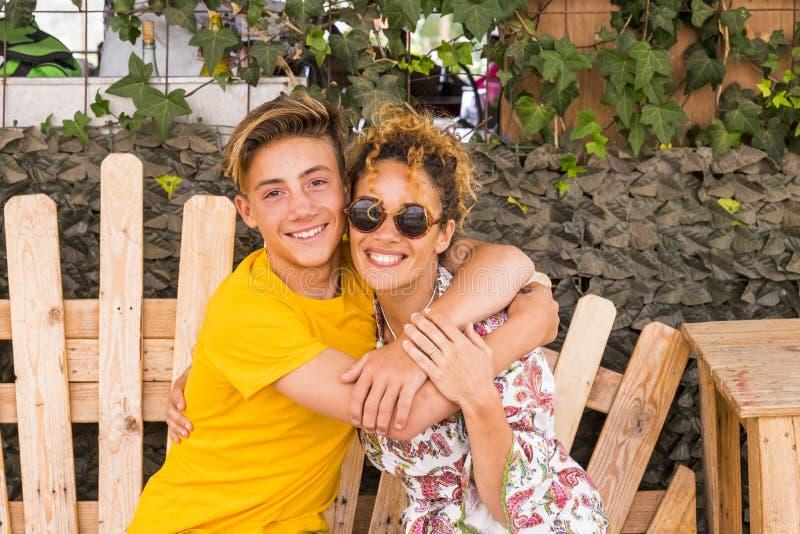 Matki i syna przytulenie z uśmiechem i cieszy się wolnego czas wraz z miłością rodzinny nastolatek chłopiec 14 lat 43 i mama zaba zdjęcia royalty free
