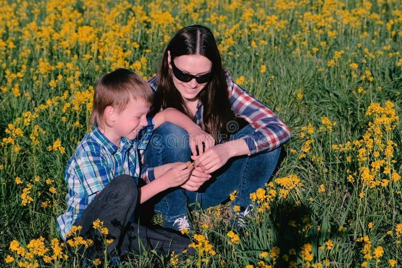 Matki i syna sztuka z kolorów żółtych kwiatami siedzi w trawie Rodzinny publiczny występ fotografia stock