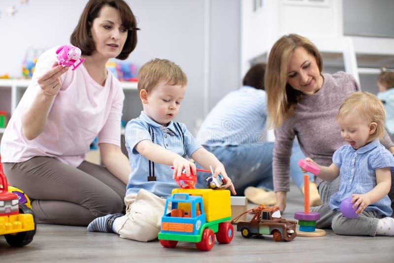 Matki z ich dziećmi bawić się zabawki w daycare centre obraz royalty free