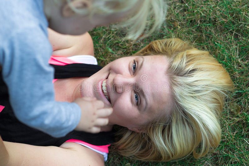 Matkuje nastroszony nadmiernego jej dziecko ono uśmiecha się i kłama na trawie, zdjęcie royalty free
