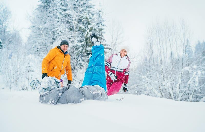 Matkuje rodziny błaź się w śnieżnym lesie rzucać ich małego syna snowdrift i ojcuje obraz stock