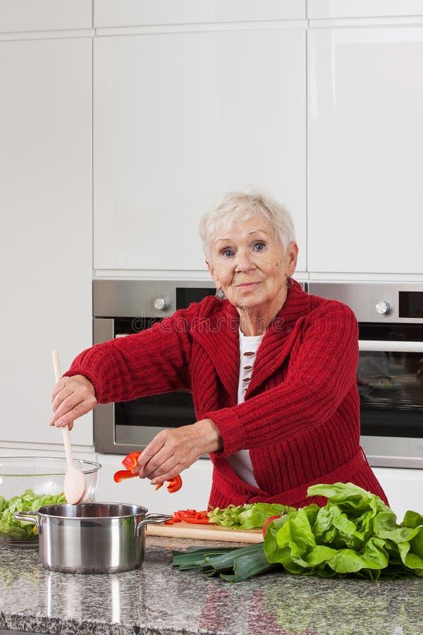Matlagning för äldre dam royaltyfri foto