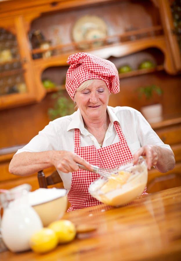 Matlagning för hög eller äldre kvinna i kök arkivfoton