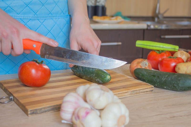Matlagning f?r ung kvinna i k?ket Kantjusterad bild av bitande gr?nsaker f?r ung flicka f?r mat Kocken klipper gr?nsakerna in i e arkivbilder