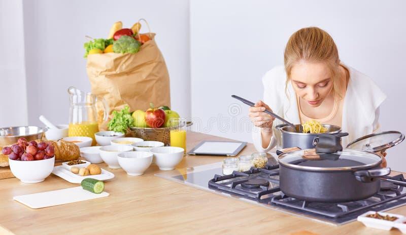 Matlagning f?r ung kvinna i k?ket sund mat royaltyfria foton