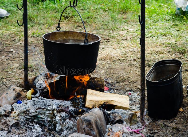 Matlagning i en vandring i kitteln som hänger över branden arkivbild