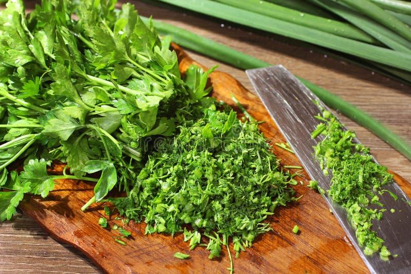 Matlagning i k?ket gr?nska Vegetablesisolated gr?n onions Kniv och sk?rbr?da fotografering för bildbyråer