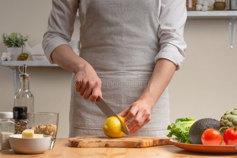 matlagning Kocken klipper en citron i processen av en vegetarisk sallad i det hem- köket Ljus bakgrund Restaurangmeny, meny, arkivbild