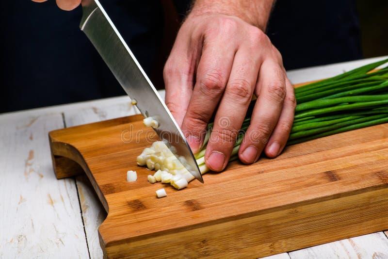 matlagning Kocken klipper salladslöken i köket royaltyfri bild
