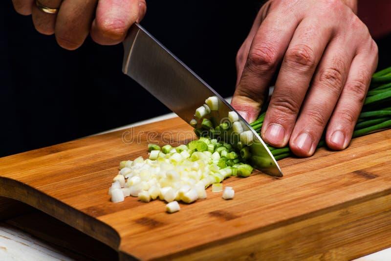 matlagning Kocken klipper salladslöken i köket arkivfoton