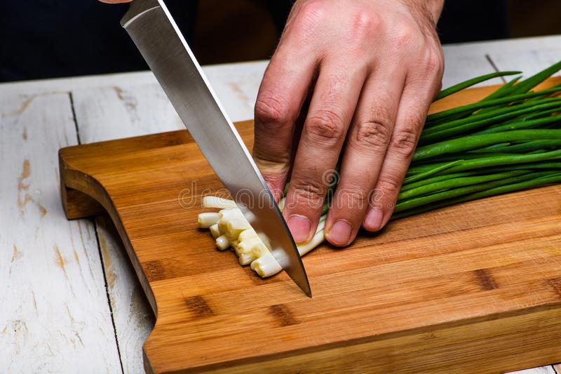 matlagning Kocken klipper salladslöken i köket arkivbilder