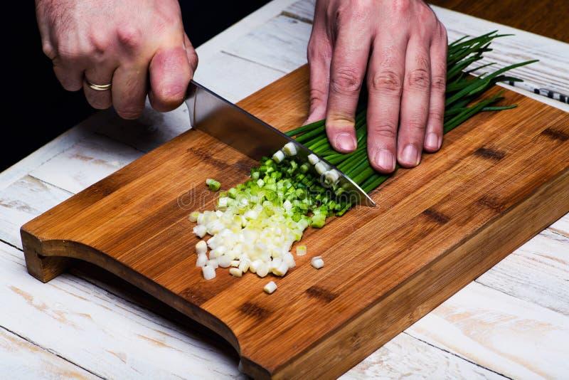 matlagning Kocken klipper salladslöken i köket royaltyfria bilder