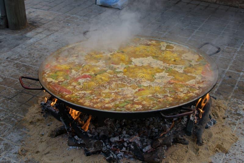Matlagning och danande en traditionell spansk paella över öppen brand med brandträ och kol Traditionell maträtt av Valencia, Span royaltyfria bilder