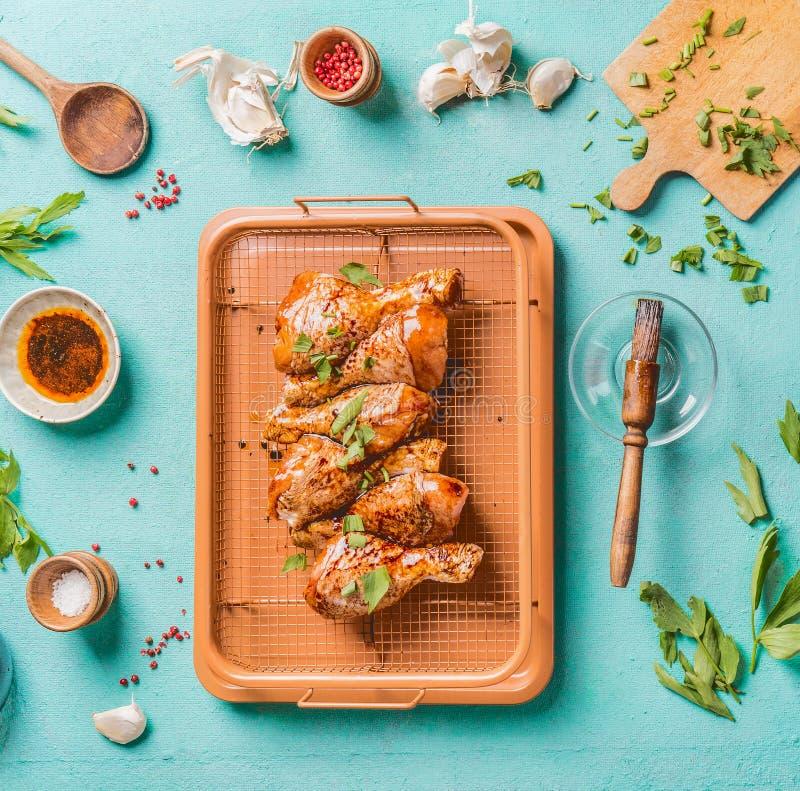 Matlagningförberedelse av rå fega trumpinnar Rå marinerade fega ben på gallerraster med ingredienser, örter, kryddor, sås royaltyfria bilder