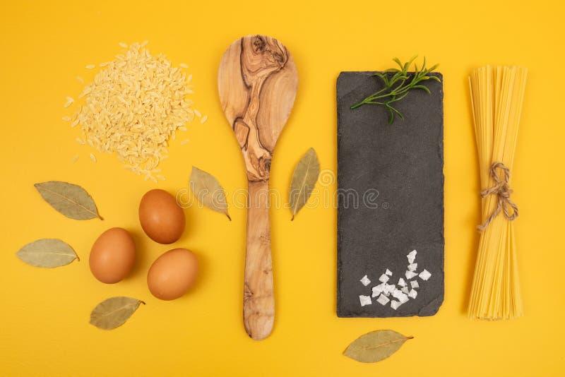 Matlagningingredienser på ljus gul bakgrund arkivbilder