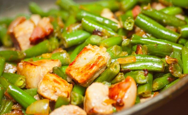 Matlagningkött med haricot vert i panna royaltyfri foto