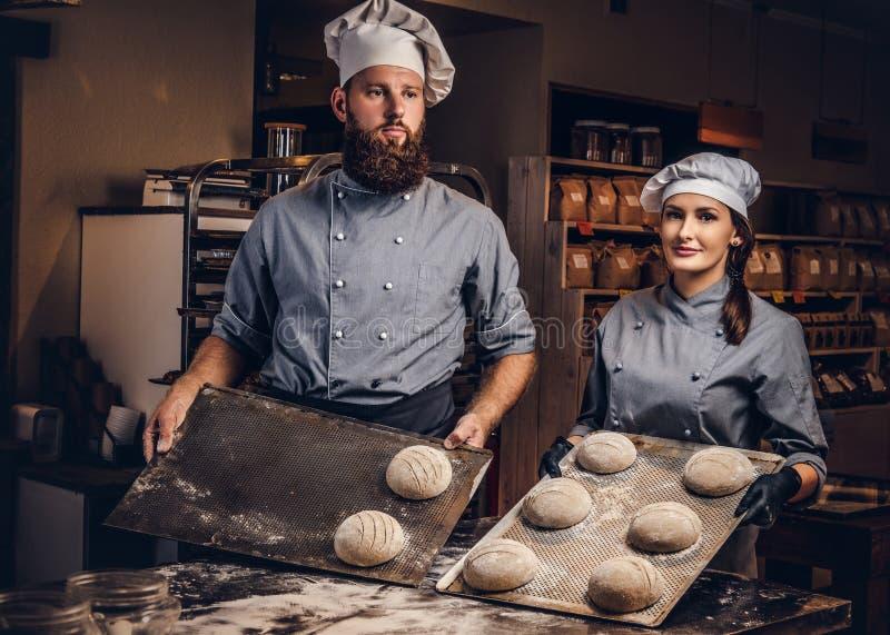 Matlagningmästarklass i bageri Kock med hans klara prövkopior för assistentvisning av det stekheta provet i kök arkivbilder