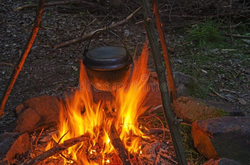 Matlagningmatställe i kittelkruka över en öppen brand fotografering för bildbyråer