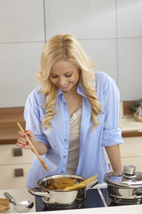 Matlagningspagetti för ung kvinna royaltyfri foto