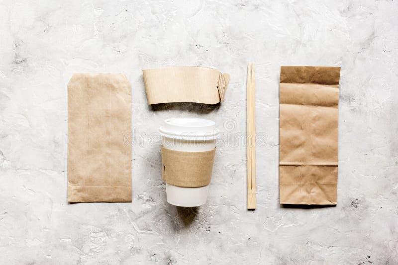 Matleveransen med pappers- påsar och den plast- koppen på stenen bordlägger modellen för den bästa sikten för bakgrund royaltyfria foton