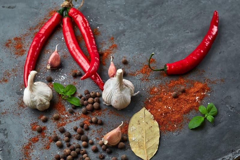 Matmatlagningbakgrund med chilipeppar, vitlök och kryddor på den mörka stentabellen royaltyfri fotografi