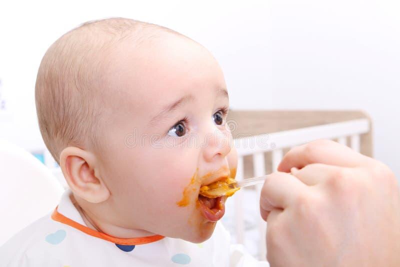 Matning av en behandla som ett barnpojke arkivfoton