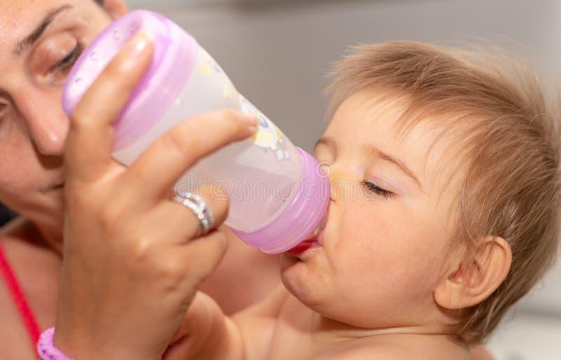 matning moder Behandla som ett barn Flaska Äta gulligt royaltyfria bilder
