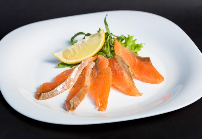 Maträtt av den röda fiskfilén för skivor med citronen och gräsplaner arkivbild